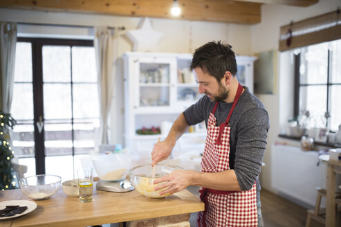 Man standing in kitchen, preparing cake dough - HAPF01333