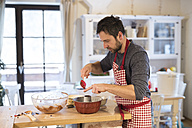 Man standing in kitchen baking ring cake - HAPF01351