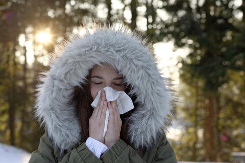Teenage girl wearing hooded jacket blowing her nose in winter - LBF01548