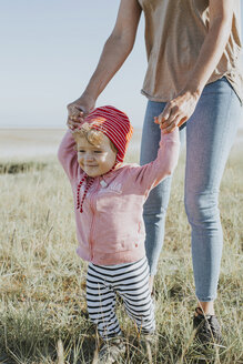 Smiling toddler holding mother's hands on a meadow - DWF00272