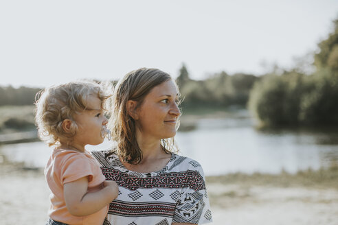 Netherlands, Schiermonnikoog, mother and little daughter watching something near the lake - DWF00278