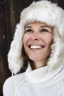 Portrait of smiling woman wearing fur cap in winter looking up - FSF00730