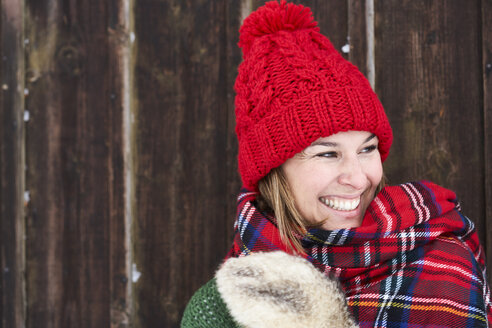 Portrait of smiling woman wearing red bobble hat in winter - FSF00736