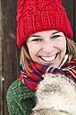 Portrait of happy woman wearing red bobble hat in winter - FSF00739