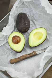Whole and sliced avocado and kitchen knife on parchment paper - JUNF00814
