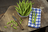 Whole and chopped green beans, cloth and kitchen knife on wooden board - JUNF00826