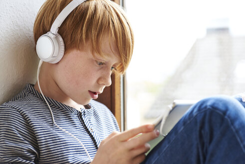 Boy sitting on window sill using digital tablet, wearing head phones - JEDF00277