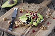 Protein bread slice with cream cheese, sliced avocado, walnuts and  pomegranate seed on wooden board - YFF00636