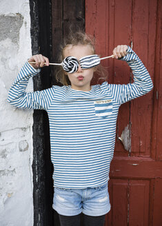 Girl covering eyes with licorice lolly pops - OJF00182