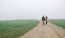 Couple walking on a path on a foggy winter day - DAPF00554