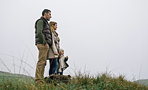 Family with dog standing on a meadow on a foggy winter day - DAPF00557