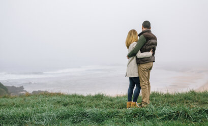 Couple hugging at the coast on a foggy winter day looking at view - DAPF00560