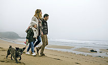 Family walking with dog on the beach on a foggy winter day - DAPF00563