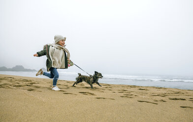 Happy girl running with dog on the beach on a foggy winter day - DAPF00566