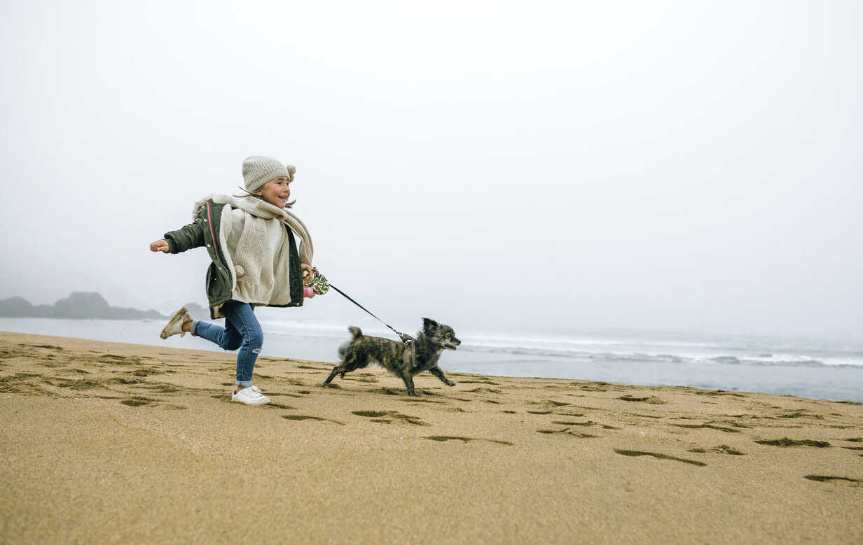 Happy girl running with dog on the beach on a foggy winter day - DAPF00566 - David Pereiras/Westend61