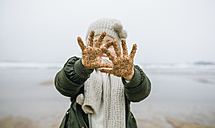 Girl showing her sandy hands on the beach in winter - DAPF00575