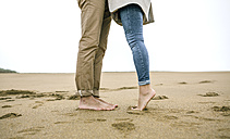 Low section of couple standing barefoot on the beach - DAPF00584