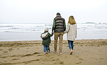 Family walking with dog on the beach in winter - DAPF00587
