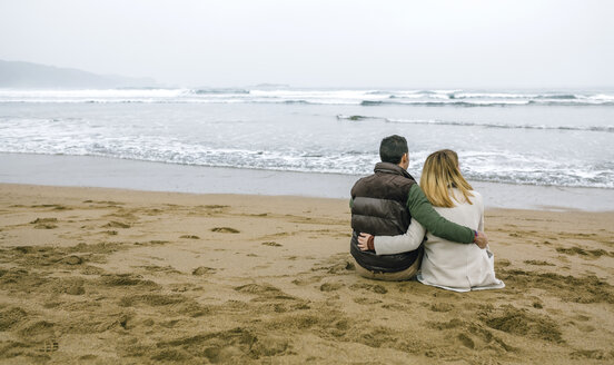 Couple in love sitting on the beach in winter - DAPF00590