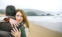 Woman embracing man on the beach in winter - DAPF00596