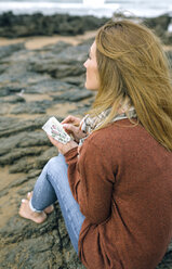 Woman with notebook sitting on rocks on the beach in winter - DAPF00602