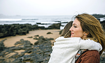 Mother holding daughter on the beach in winter - DAPF00605