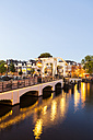 Netherlands, Amsterdam, view to  Magere Brug with Amstel River in the foreground at evening twilight - WDF03883