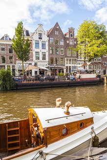 Netherlands, Amsterdam, Prinsengracht, cafe on ship and old wooden motorboat on town canal - WD03898