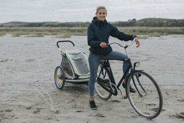 Netherlands, Schiermonnikoog, woman with bicycle and trailer on the beach - DWF00287