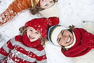 Mother and daughters lying on snow, having fun - FSF00774