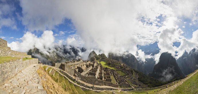 Peru, Andes, Urubamba Valley, Machu Picchu with mountain Huayna Picchu in fog with tourists - FOF08815