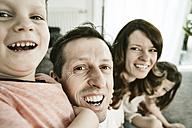 Happy family sitting at home on couch - JATF00947