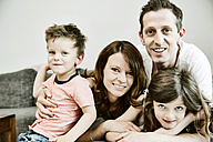 Happy family sitting at home on couch - JATF00956