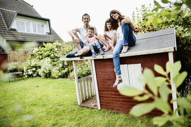 Happy family sitting on roof of their garden shed - JATF00962
