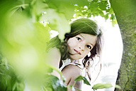 Girl crouching behind tree, looking at camera - JATF00968