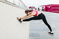 Young woman stretching and warming up for training at the beach - GIOF01734