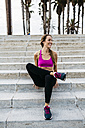 Young woman sitting on stairs after training - GIOF01743