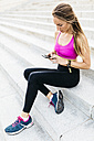 Young woman sitting on stairs after training, using smart phone - GIOF01746