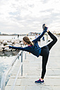 Young woman doing yoga poses at the the beach - GIOF01752