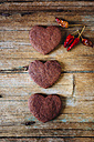 Three heart-shaped chocolate shortbreads and dried chili pods on wood - GIOF01758