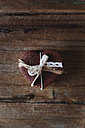 Stack of heart-shaped chocolate shortbreads tied with lace on wood - GIOF01761