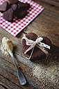 Stack of heart-shaped chocolate shortbreads tied with lace and tea spoon of brown sugar on wood - GIOF01764