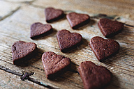 Nine heart-shaped chocolate shortbreads in rows on wood - GIOF01767
