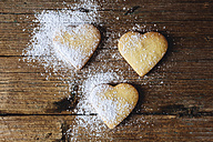 Three heart-shaped shortbreads sprinkled with icing sugar on wood - GIOF01773