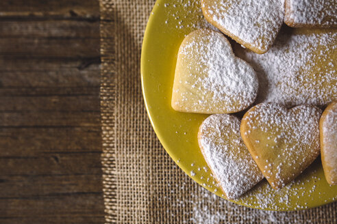 Heart-shaped shortbreads sprinkled with icing sugar on yellow plate - GIOF01776