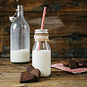 Glass bottle of milk and heart-shaped chocolate shortbread on wood - GIOF01782