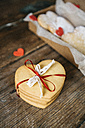 Stack of four heart-shaped shortbreads tied with lace and ribbon on wood - GIOF01788