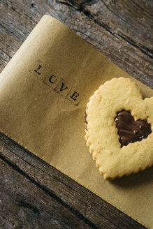 Heart-shaped Shortbread with chocolate filling on paper with the word 'love' - GIOF01797