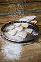 Sprinkling heart-shaped shortbreads with icing sugar on baking pan - GIOF01800