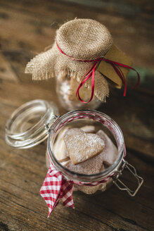 Glass of heart-shaped shortbreads sprinkled with icing sugar on wood - GIOF01806